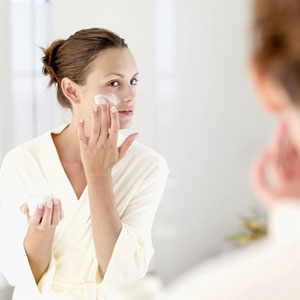 woman applying cream in mirror