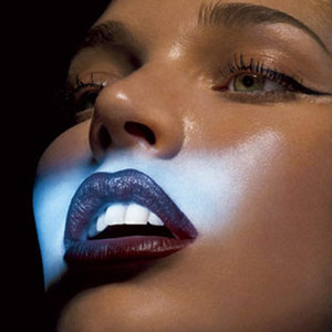 woman with dark lipstick white teeth and light shining on her face